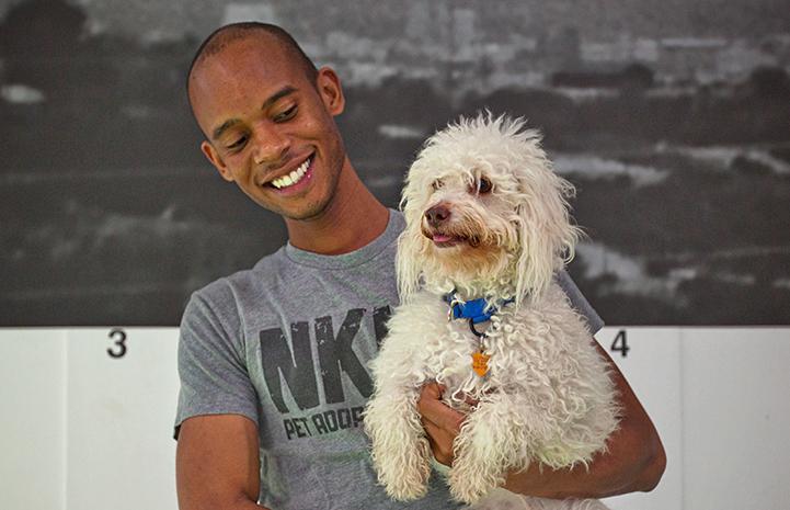 Man wearing a NKLA T-shirt holding a fluffy white dog