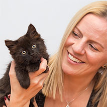 Woman holding a black kitten