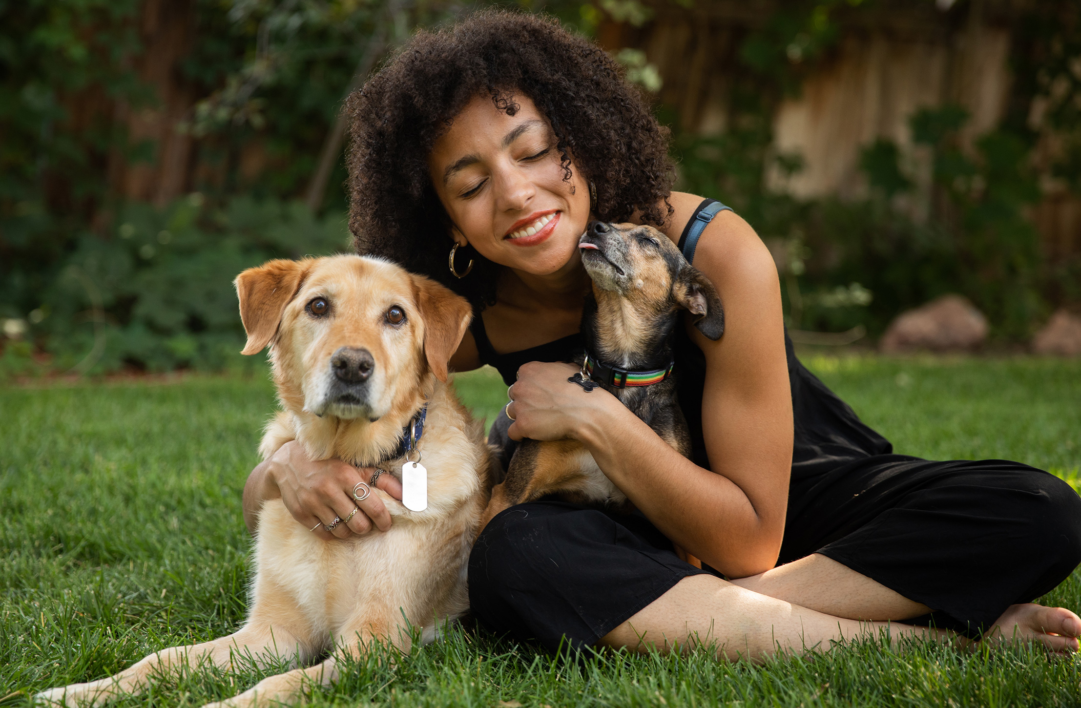Smiling woman hugging a yellow Lab and getting kissed on the chin by a small dog who she's holding