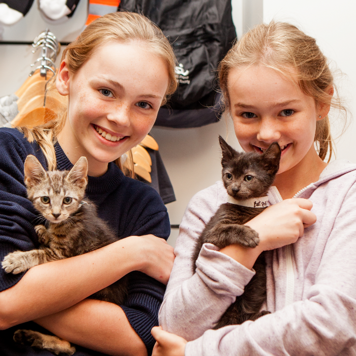 Two young girls holding kittens at Best Friends event