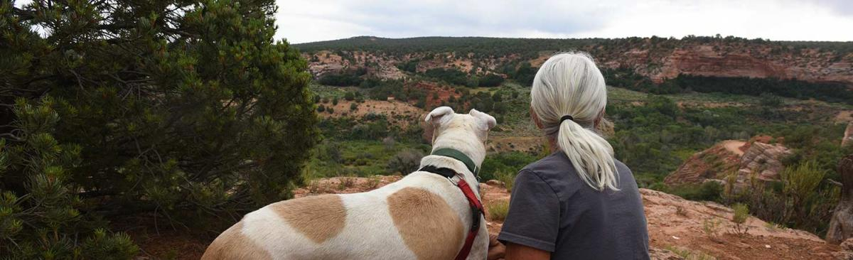 Woman and dog looking out over a bluff at Angels Canyon