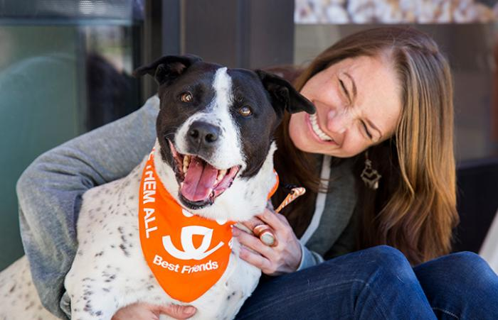 Smiling woman holding a smiling black and white dog who is wearing a Best Friends bandanna