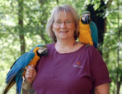 Woman holding two blue and gold macaws, one on her hand and another on her shoulder