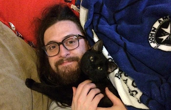 Bearded man cuddling with black cat