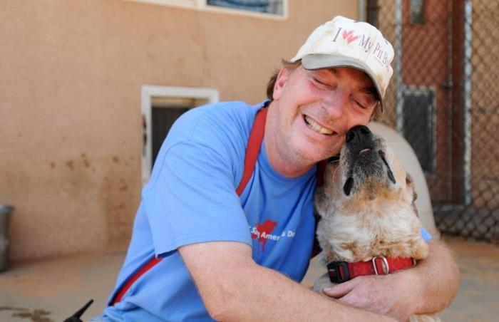 Fred the dog, who has been trained using hand targeting, receives a hug from Tom