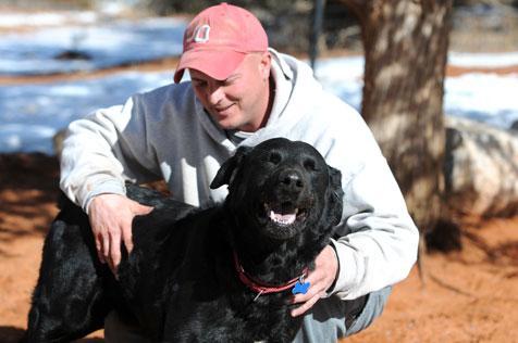 Black Labrador retriever mix Archie with his caregiver Josh