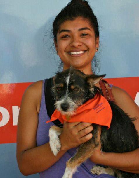 Adopter holding a small dog wearing a bandana