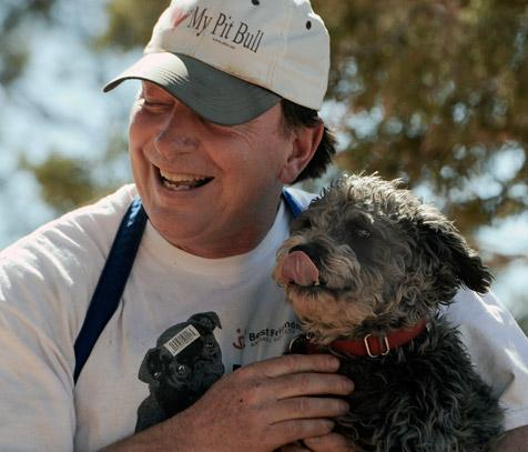 Gordo the dog who hated men posing with a man for a photo