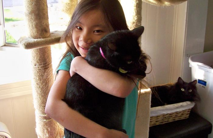 Little girl Violet Schultz snuggles a cat at Best Friends Animal Sanctuary