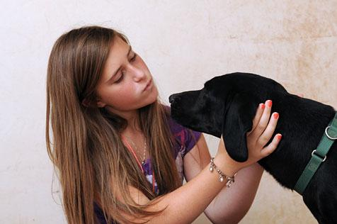 Young girl Mariah and Seager the black Lab retriever mix