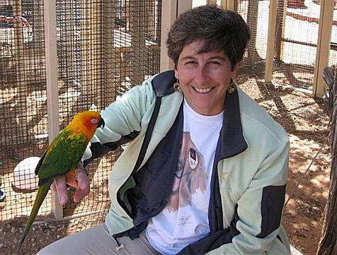 Dr. Julie Palais with a parrot on her arm at Best Friends Animal Sanctuary