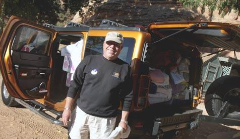 Retired Marine Tom Fuller in front of his Hummer full of donations for animals
