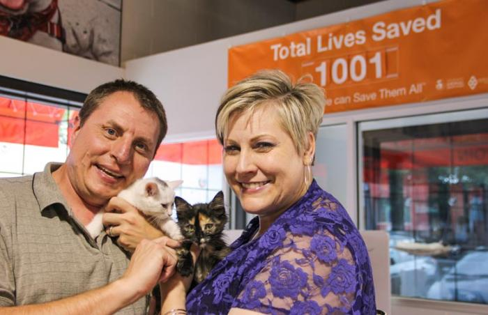 Couple at Best Friends Pet Adoption Center in Salt Lake City, Utah, holding two cute kittens they adopted