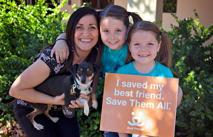 "The Donnelly family with Mozart the dog. A little girl is holding a sign that reads, ""I saved my best friend. Save Them All."""