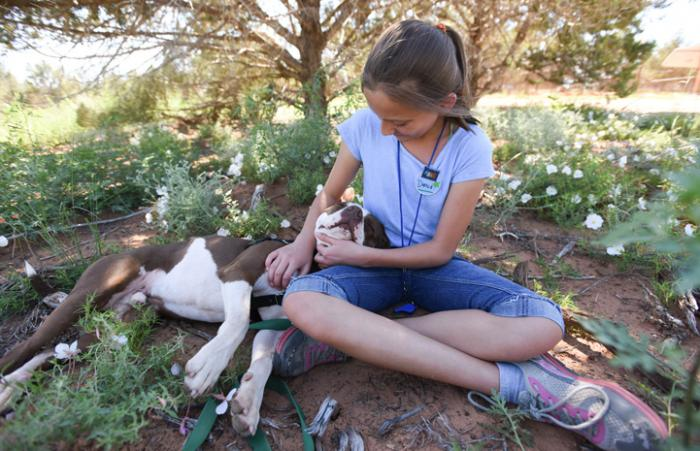 Preteen Danica snuggling with Phinny the dog while volunteering at Best Friends Animal Sanctuary