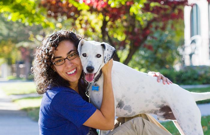 Woman hugging a black and white dog