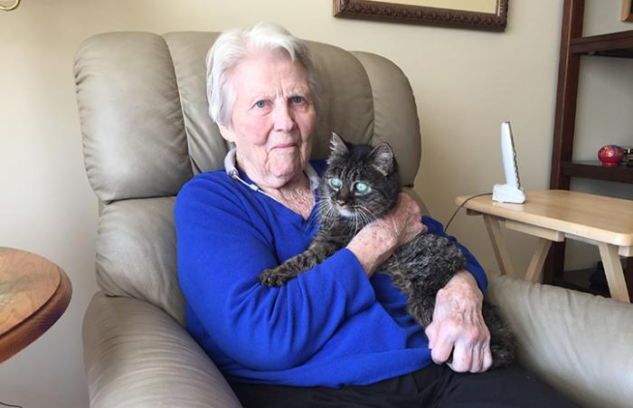 Jan, sitting on a chair at her senior living facility holding Daisy the senior brown tabby cat