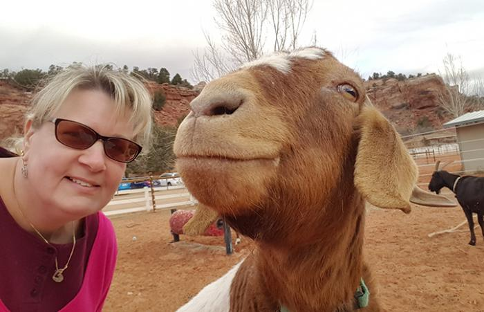 Volunteer Sheri Slattery posing with Danielle, a brown and white goat