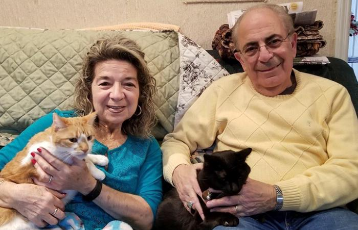 Lucy and Ray Tocci with newly adopted Pyro and Raoul the cats on their laps