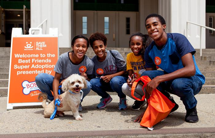 Family adopting Benji the small white dog in front of a Best Friends Super Adoption sign