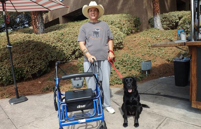 Veteran Sue Wright in a cowboy hat standing next to her service dog Lady Diana