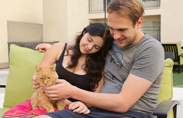 Mari and her husband John holding Lionel the senior orange tabby cat
