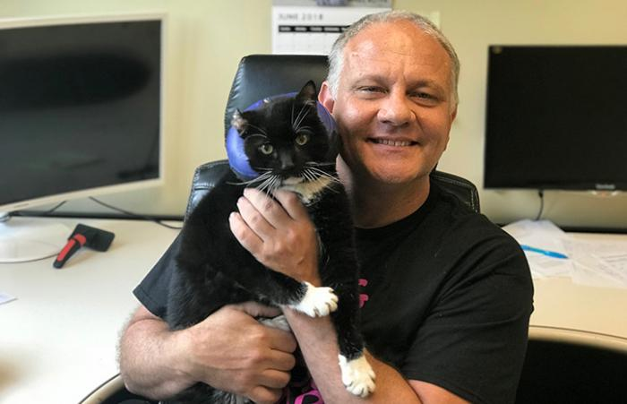 Tom Hubric holding Marvin the black and white cat
