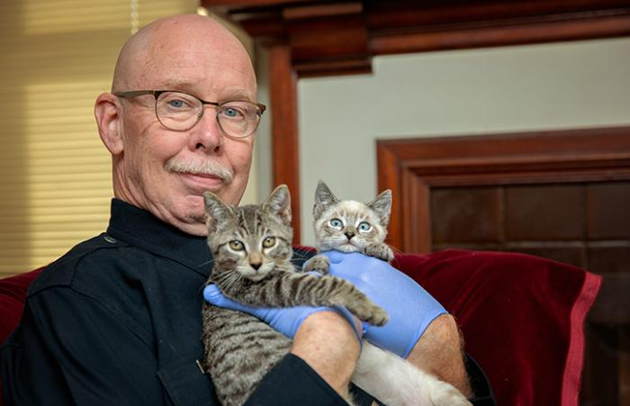 Volunteer Michael Moran holding two of his foster kittens in a gloved hand