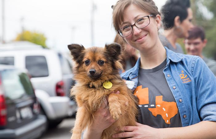 Smiling woman wearing Best Friends shirts holding a small brown fluffy dog named Mick