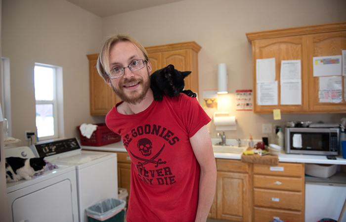 Carly the black cat sitting on a man's shoulder