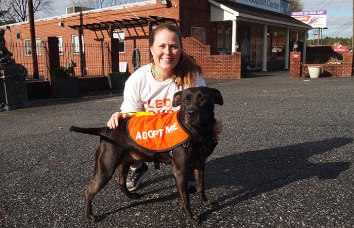 Volunteer Sandy Saffold posing with a black dog wearing an Adopt Me vest, by the Best Friends Lifesaving Center in Atlanta