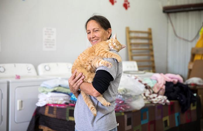 Smiling woman holding an orange tabby cat on her shoulder