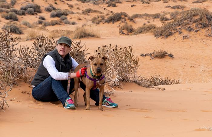 Person sitting in the sand with Rad the dog