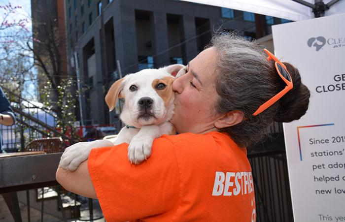 Volunteer Deyra Galvan wearing an orange Best Friends T-shirt and holding and kissing a white and tan puppy