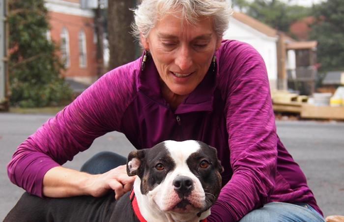 Woman wearing purple jacket squatting down to pet black and white dog