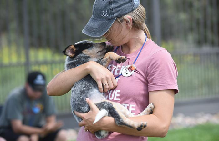Woman wearing a hat and Best Friends volunteer pin cradling a puppy in her arms