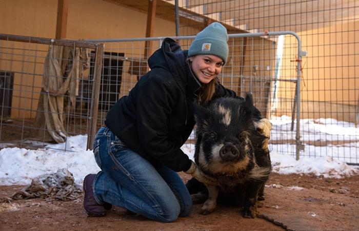 High school volunteer Abby Leuchten with Petunia the potbellied pig