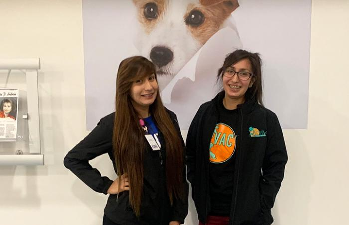 Yessy and Yobeli Banda, sisters who work at Palm Valley Animal Center (PVAC) in Edinburg, Texas, standing under a puppy photo