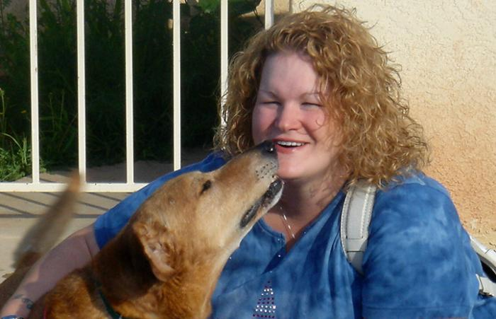 Senior dog Arby giving a kiss to smiling woman