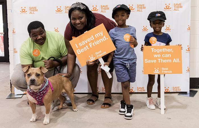 Family with the dog they just adopted, standing in front of a Best Friends backdrop, while holding adoption signs