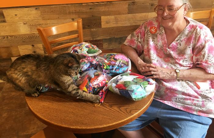 Volunteer Marilyn Mott with her bags of donated mouse shaped cat toys, while torbie cat plays with one of the toys