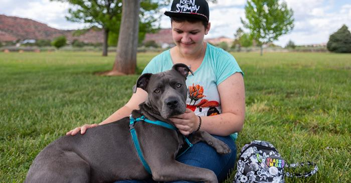 Woman sitting on the grass with Chunk the gray dog lying on her lap