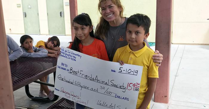 Woman posing with two kids holding a giant check for Best Friends Animal Society