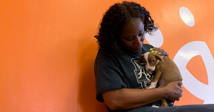 Volunteer Faye Robinson cradling a small puppy against her chest