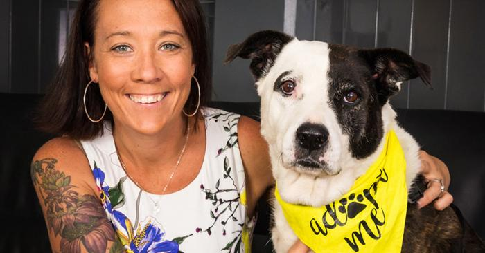 Kristen Hassen-Auerbach next to a black and white dog wearing a yellow Adopt Me bandanna