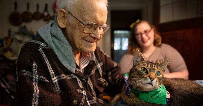 Senior man engaging with Hercules the therapy cat while a woman watches