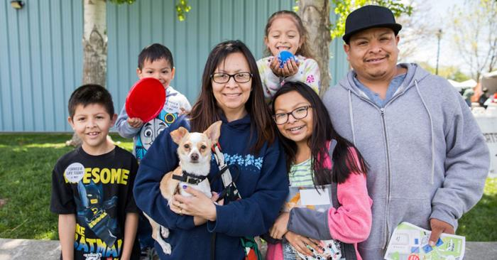 Family holding a blond Chihuahua dog