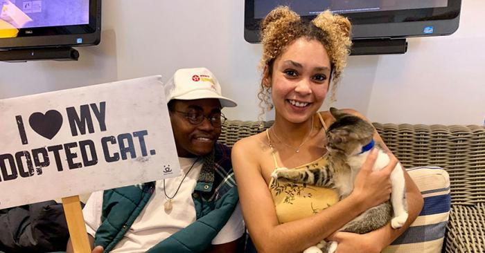 Smiling woman holding a cat with a man behind her holding a sign that says, I love my adopted cat