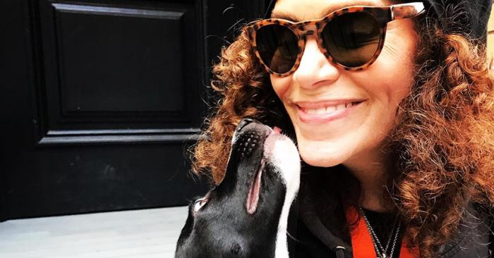 Volunteer Lauren Fishman smiling and getting kissed by a black and white dog