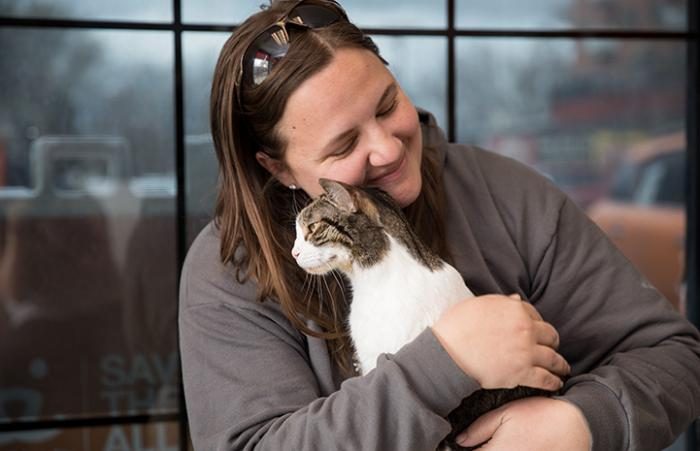 Smiling woman hugging a tabby and white cat